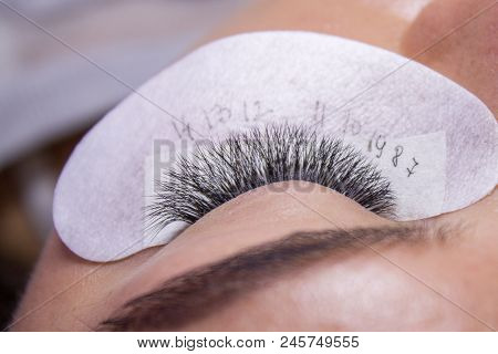 Beauty And Fashion Concept - End Of Eyelash Extension Procedure. Woman Eye With Long False Eyelashes