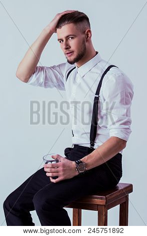 Stylish And Elegant Man In White Shirt And Suspenders Keeping Hand In Hair And Glass Of Whiskey In A