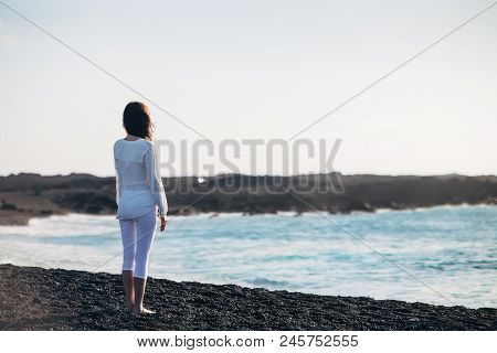 Back view of young lonely woman enjoying ocean on black sand beach. Canary Islands, Spain. Solitude concept poster