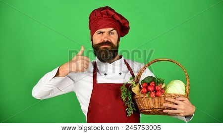 Colorful Culinary Concept. Confident Young Chef With Beard In Burgundy Uniform Holding Multi Colored
