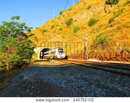 Alora, Spain - May 14, 2018: Malaga To Seville Train Emerging From Tunnel On Electric Track Near Alo