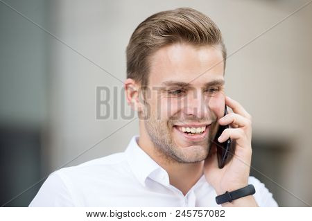 Always Available. Man Well Groomed White Shirt Speak Phone Urban Background. Guy Handsome Attractive