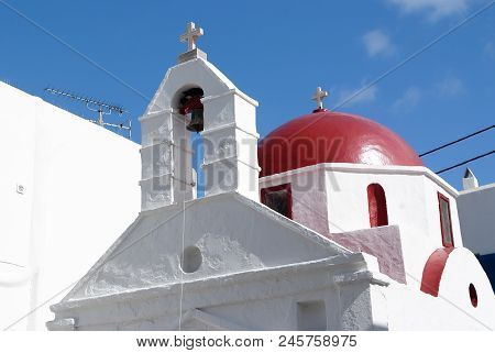White Church Architecture In Mykonos, Greece. Chapel With Bell Tower And Red Dome. Church Building O