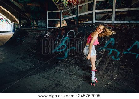A Picture Of Well-built Rollerblaider Riding Backwards. She Is Looking Back Careful. Girl Is Smiling