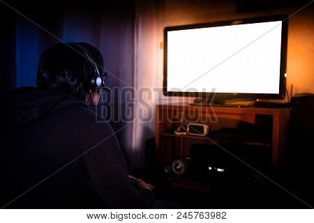 Young Male Gamer With Glasses And Headset Playing Video Game At Home In The Dark Room Using Game Con