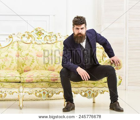 Macho Attractive And Elegant On Serious, Thoughtful Face Sitting On Old Fashioned Luxury Sofa. Fashi