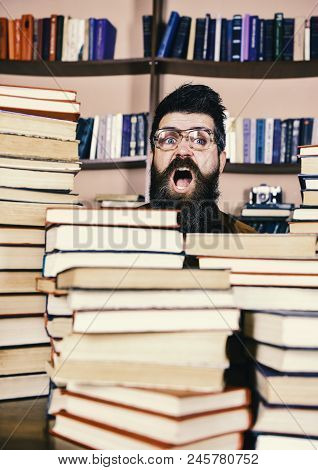 Teacher Or Student With Beard Wears Eyeglasses, Sits At Table With Books, Defocused. Nerd Concept. M