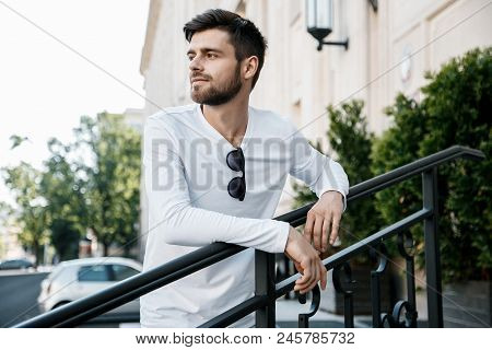A Young Man Travels Through The Streets Of The City. Boy In Sunglasses Stylish Man Near The Building