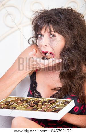 Woman Crying And Eating Chocolates From A Box In Her Bedroom