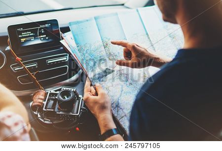 Hipster Man Looking And Point Finger On Location Navigation Map In Car, Tourist Traveler Driving And