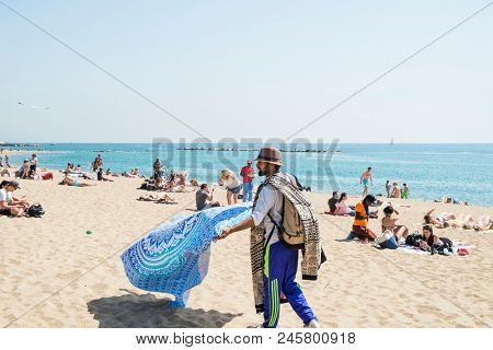 BARCELONA, SPAIN - APRIL 27, 2018: Sunbathers at the Barceloneta Beach in Barcelona, Spain, and a hawker selling beach wraps in the foreground