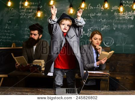 Pupil With Blurred Mother And Father At Chalkboard, Family. Pupil Boy In Big Suit Coat And Graduatio