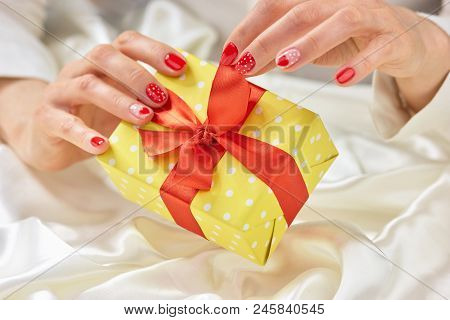 Girl Hands Unpacking Present Box. Gentle Female Hands Is Opening Gift Box With Red Bow.