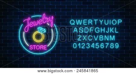 Jewelry Store Glowing Neon Signboard With Alphabet On Dark Brick Wall Background. A Ring With Big Di