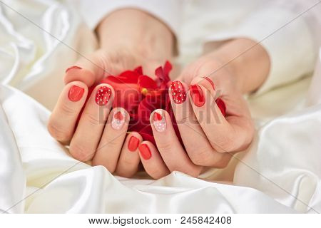 Rose Petals In Female Hands. Female Hands Holding Red Rose Petals. Red Romantic Manicure.
