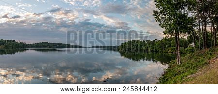 Banner Image Of Clouds Colored At Sunset On A Calm Lake With Wooded Shoreline.