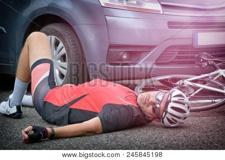 Cyclist lying on the road after an accident involving a car and a bicycle