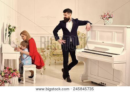 Joy Of Parenting. Home Schooling Concept. Father Stands Near Piano, Watching While Mother Teaches So