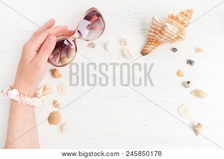 Attributs Of Summer Vacations. Pink Glasses In Female Hand With Different Shells On The White Wooden