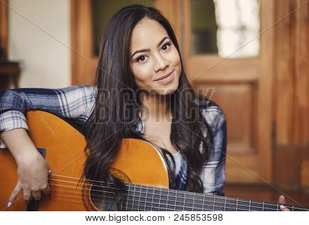 Close Up Portrait Of Beautifu Hispanic Woman Singer Holding Acoustic Guitar Indoors, Copy Space
