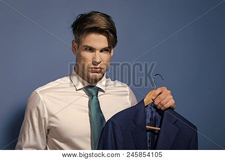 Serious Man In A Suit. Man In White Shirt, Necktie Hold Jacket On Hanger On Blue Background. Busines