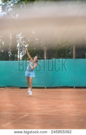 Pretty Girl Plays Tennis On The Court Outdoors. She Just Beaten Off A Ball During A Jump. Woman Wear