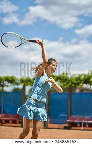 Charming Girl Plays Tennis On The Court Outdoors. She Prepares To Beat Off A Ball. Woman Wears A Lig