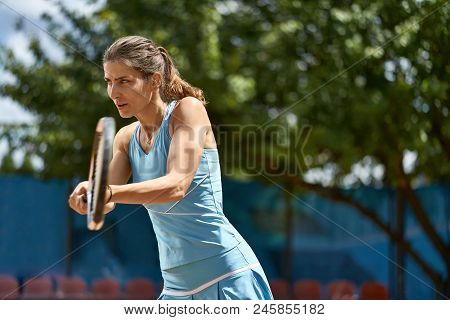 Athletic Girl Plays Tennis On The Court Outdoors. She Prepares To Beat Off A Ball. Woman Wears A Lig