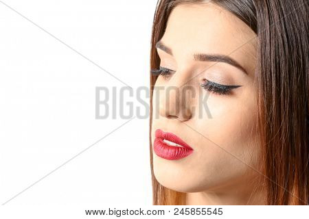 Attractive young woman with elegant makeup and long eyelashes on white background. Eyelash extensions