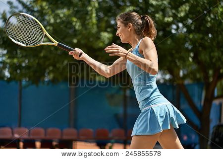 Smiling Girl Plays Tennis On The Court Outdoors. She Prepares To Beat Off A Ball. Woman Wears A Ligh