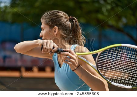 Beautiful Girl Plays Tennis On The Court Outdoors. She Prepares To Beat Off A Ball. Woman Wears A Li