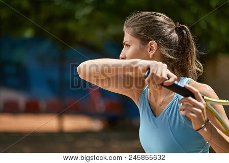 Pretty Girl Plays Tennis On The Court Outdoors. She Prepares To Beat Off A Ball. Woman Wears A Light