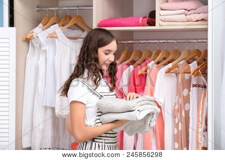 Teenage girl putting clothes into wardrobe at home