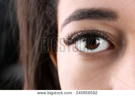 Attractive African-American woman with long eyelashes, closeup. Eyelash extensions