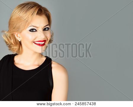 Portrait Of Blonde Girl With Evening Makeup On Gray Background. Beautiful Makeup And Black Dress. Sk