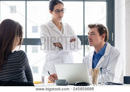 Young nurse listening to an experienced physician while consulting a female patient in the office of a modern hospital