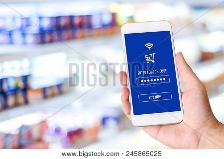 Hand Holding Smartphone With E-coupon, Discount Coupon On Screen Device Over Blur Grocery Background