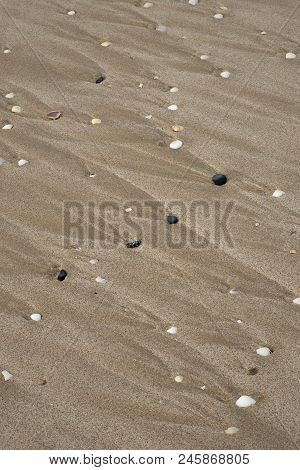 Pebbles And The Wave Lines They Created With Tidal Waters Rushing Over Them On A Sandy Beach