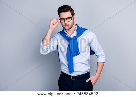 Portrait Of Cool Stunning Guy With Tied Blue Sweater Around Neck, Holding Hand In Pocket Of Pants An