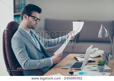 Portrait Of Thoughtful Stylish Financier Holding Papers In Hand, Expertising Documents, Working On S