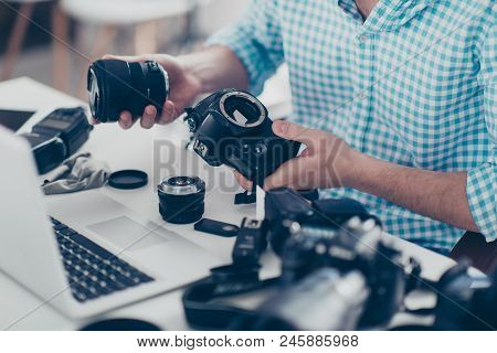 Cropped Non Face Portrait Of Man In Shirt Holding Camera And Lens In Hands Sitting At Desktop, Havin