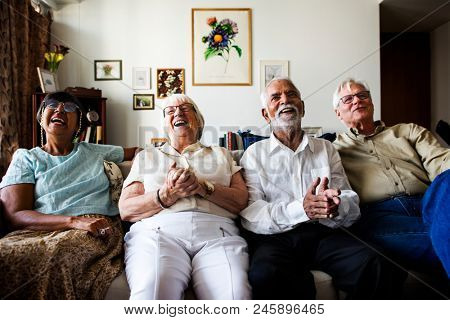 Group of senior friends sitting and watching tv together