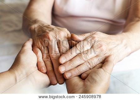 Mature Female In Elderly Care Facility Gets Help From Hospital Personnel Nurse. Senior Woman W/ Aged