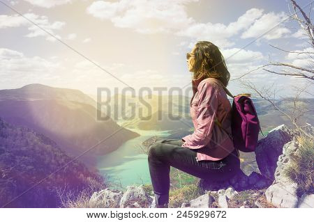Girl Relaxing On A Beautiful Mountain View. Traveler Sitting On Mountain Rock Enjoying Beautiful Mou