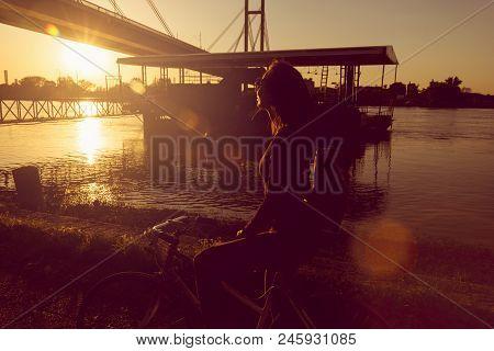 Girl Feeling Free In City Bike Ride In Sunset. Girl On A Bike. Sunset Bike Ride. Young Woman On A Bi