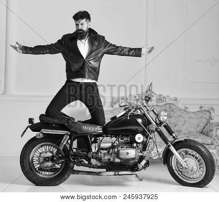 Man Biker In Leather Jacket Near Motor Bike In Luxury Living Room Interior Background. Hipster Biker