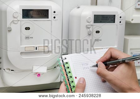 Electric Energy Meter. Man Notes The Meter Reading. Increase In Electricity Bills Concept