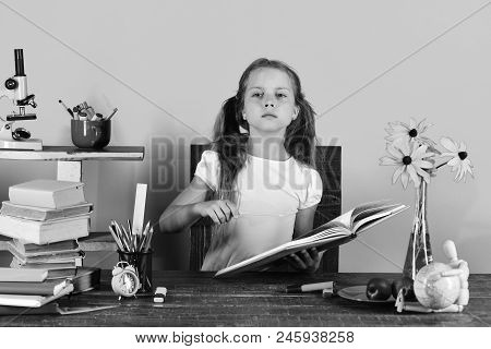 Back To School Concept. Schoolgirl Sits At Desk With Colorful Stationery, Books, Globe, Clock And Fl