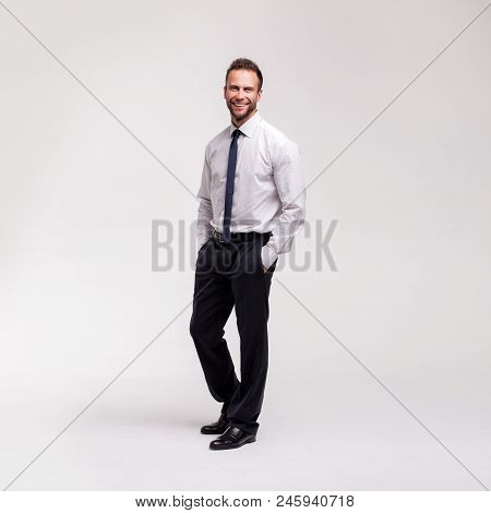 Portrait Of Young Handsome Smiling Businessman Wearing Black Suit Isolated On White Studio Backgroun
