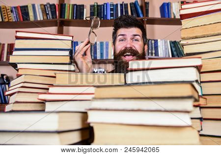 Man On Happy Face Between Piles Of Books In Library, Bookshelves On Background. Teacher Or Student W